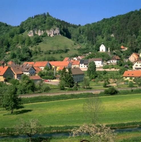 Blick auf Hütten im Hintergrund zwischen den Bäumen versteckt die Burgruine Hohenjustingen